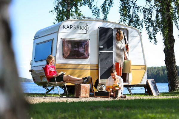 Nelihenkinen perhe hengailee asuntovaunun edessä. Asuntovaunussa lukee Kapsäkki.