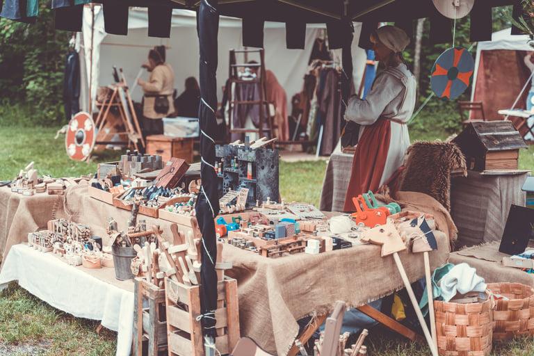 Keskiaikaisiin vaatteisiin pukeutuneita ihmisiä markkinakojulla