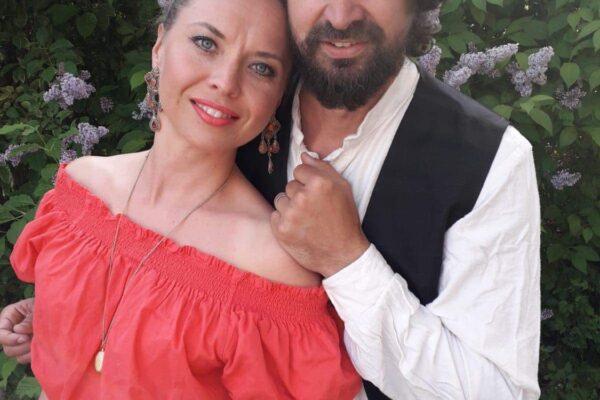 Punaiseen paitaan ja hameeseen pukeutunut nainen nojaa valkoiseen paitaan ja mustaan liiviin pukeutuneeseen mieheen.