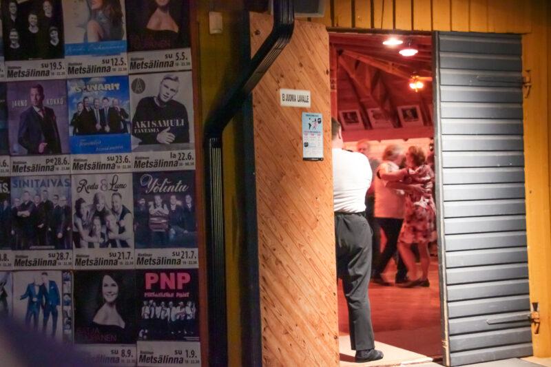 Mies nojaa tanssilavan oveen, takana näkyy tanssivia ihmisiä. Ulkoseinässä näkyy keikkajulisteita.