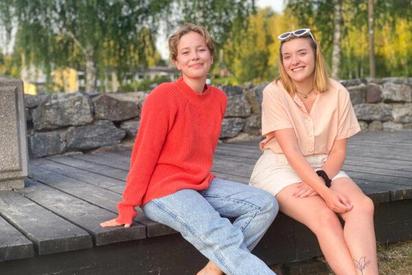 Lotta Tuominen ja Aino Halinen istuvat rantapuiston puisella kävelysillalla.