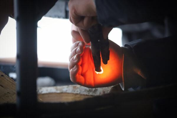 kuvassa kädet, joista toinen suojaa syttyvää tulitikkua