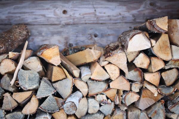 kuvassa halkopino puuseinää vastaan