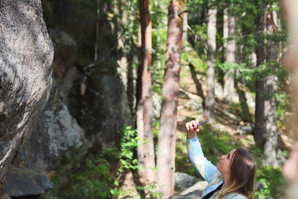 Kuvassa farkkutakkinen tyttö ottaa kännykällä kuvaa kalliomaalauksesta