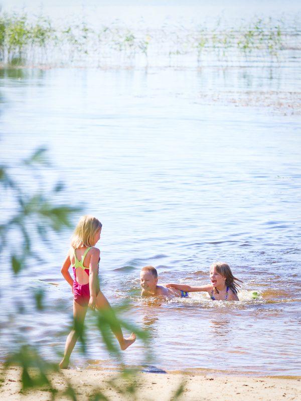 Kolme lasta leikkii rantavedessä