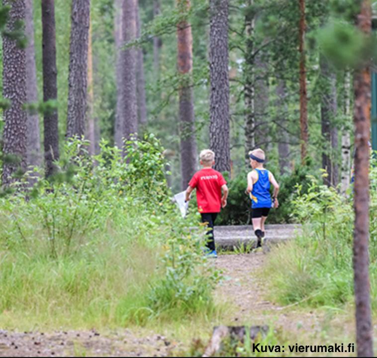 Kaksi poikaa suunnistaa metsässä