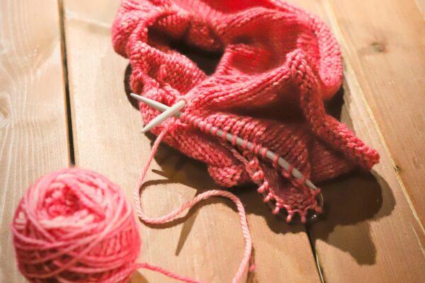 Pinkki keskeneräinen neulostyö puupöydän päällä