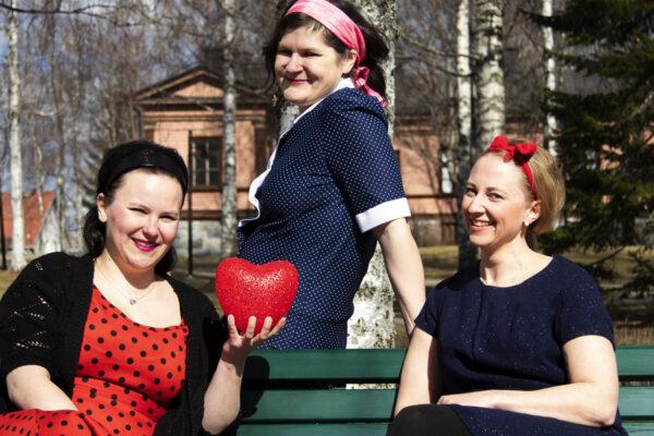 Kolme näyttelijää poseeraa kameralle 60-luvulle tyypillisissä vaatteissa
