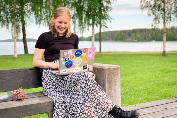 Vilma istuu puiston penkillä läppäri sylissään